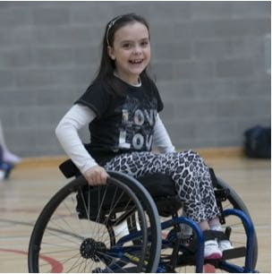 Photograph of a smiling girl in a wheelchair doing sport